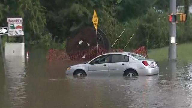School bus, cars drive through flooded Durham roads