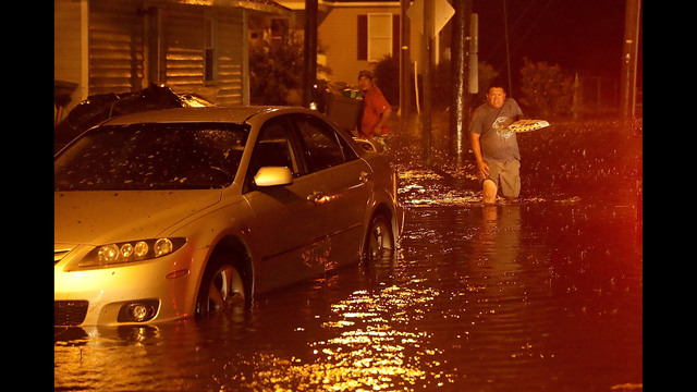 Men pack their belongings after evacuating their house after the Neuse River went over its banks and flooded their street during Hurricane Florence September 13, 2018 in New Bern, North Carolina.(Photo by Chip Somodevilla/Getty Images)