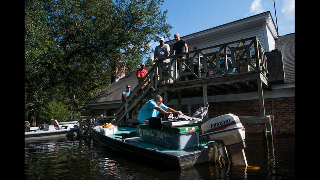 People use boats to rescue valuables from a home inundated by floodwaters caused by Hurricane Florence near the Waccamaw River. Floodwaters are expected to continue to rise in Conway over the next two days. (Photo by Sean Rayford/Getty Images)