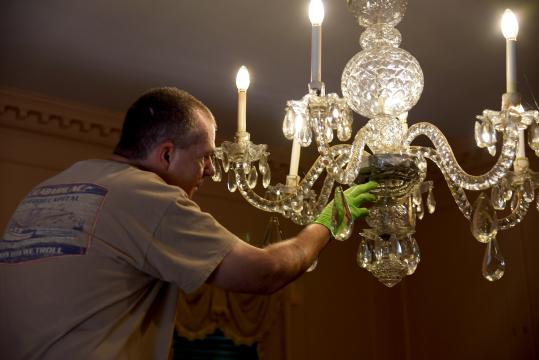 Fixing a chandelier inside the Stanly House at Tryon Palace