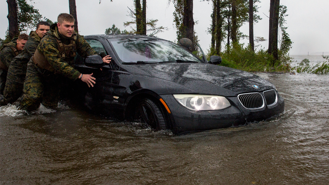 Marines with Marine Corps Base Camp Lejeune help push a car out of a flooded area during Hurricane Florence, on Marine Corps Base Camp Lejeune, Sept. 15, 2018. (Photo courtesy of U.S. Marine Corps/Lance Cpl. Isaiah Gomez)