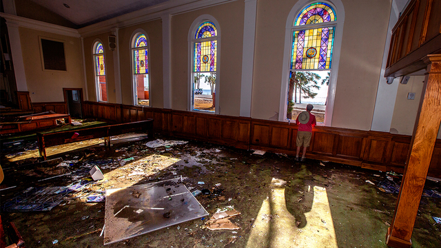 Pastor Geoffrey Lentz looks out at St Joe Bay from his sanctuary of the First United Methodist Church after it was gutted by the storm surge from Hurricane Michael on October 14, 2018 in Port Saint Joe, Florida (Photo by Mark Wallheiser/Getty Images)