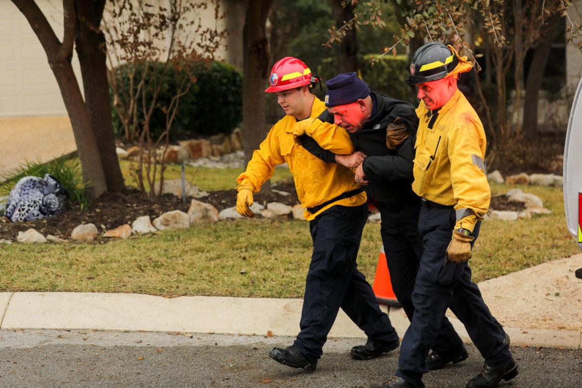 Firefighters aid a pedestrian during a simulated medical emergency involving smoke inhalation from nearby wildfires.