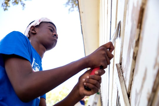 Landon Carter, 14, of Denton, scrape old paint from a house damaged by Hurricane Harvey in Aransas Pass on Wednesday, July 10, 2019. He was participating in a BOUNCE mission which offers students an opportunity to help a community that is dealing with long-term disaster recovery.