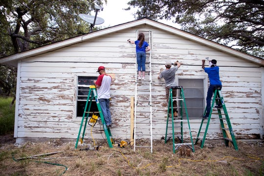Victor Lopez, from left, of Round Rock, Elli Hoskins, 12, of Plano, David Edward, 12, of Kirbyville, and Landon Carter, 14, of Denton, scrape old paint from a house damaged by Hurricane Harvey in Aransas Pass on Wednesday, July 10, 2019. The students were a few of several students in the area volunteering through BOUNCE, a ministry of Texas Baptists that was launched for students from middle-school to college to help make an impact in communities that have been impacted by disasters.