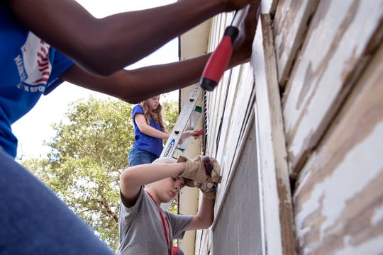 David Edward, center, 12, of Kirbyville, and Elli Hoskins, 12, of Plano, scrape old paint from a house damaged by Hurricane Harvey in Aransas Pass on Wednesday, July 10, 2019. Volunteering through BOUNCE, which was founded in 2013, the organization partners with local evangelical groups to accomplish the goal of the community rehabilitation missions.