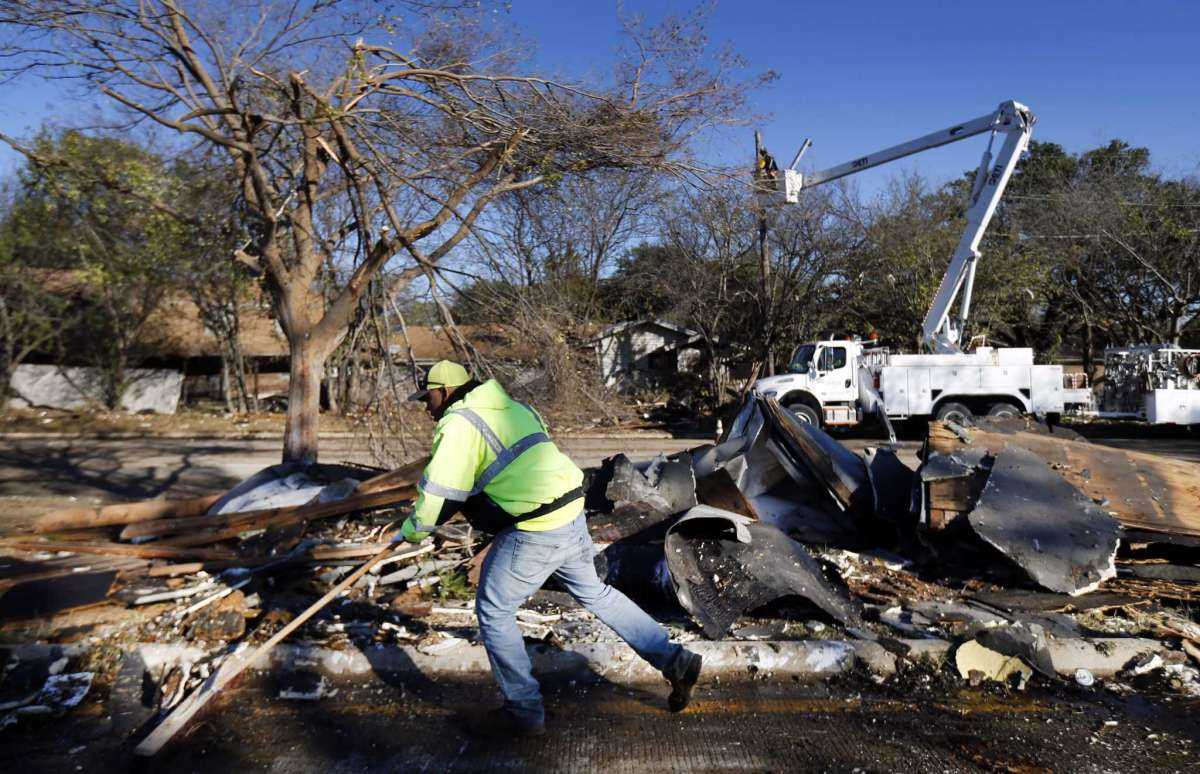 A City of Arlington street crewman cleans up debris from The Mirage Apartments complex along Pioneer Parkway in Arlington, Texas, Wednesday, Nov. 25, 2020, after a tornado-warned storm torn the roofing off. Air conditioner units and other structural debris were scattered across the property and street. The crew is trying to get the major thoroughfare open. (Tom Fox/The Dallas Morning News via AP)
