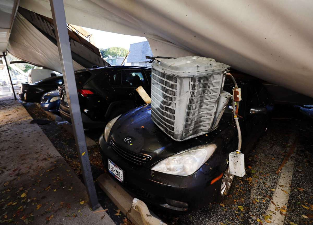 An air conditioner unit of a Waterdance Apartments building and the peeled off roof landed on a car during a tornado-warned storm that rolled through Tuesday night. Damage also occurred at The Mirage Apartments along Pioneer Parkway in Arlington, Texas Wednesday, Nov. 25, 2020. (Tom Fox/The Dallas Morning News via AP)